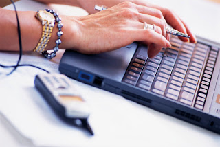 Woman Using Laptop and Cell Phone --- Image by © Royalty-Free/Corbis