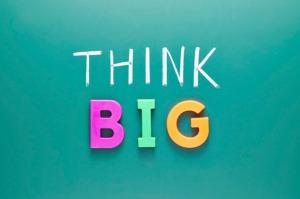 Think bigger concept, words on green blackboard