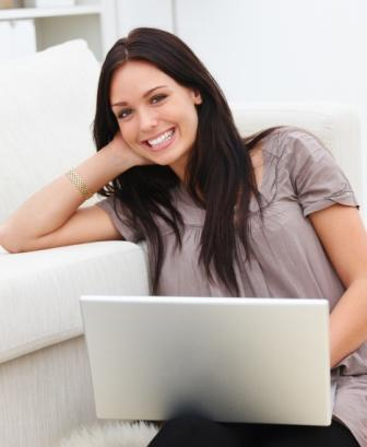Closeup of a young woman using laptop and sitting on white rug
