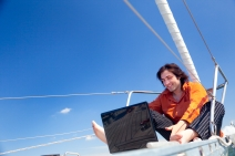 Businessman with laptop computer on sailboat